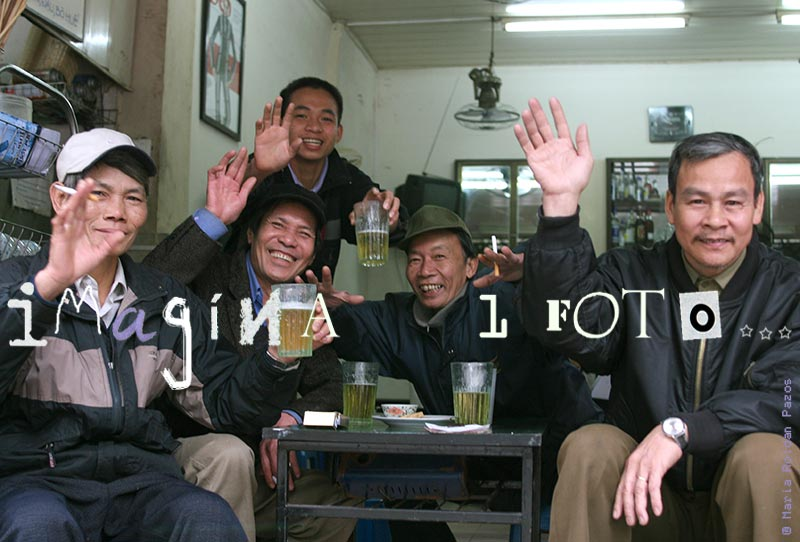 Vietnam, Hanoi, photo of a group of happy men having a beer and waving in a bar